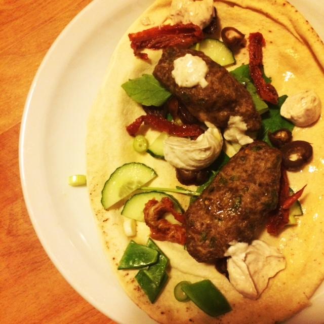 Kofte i fladbrød med dadler, tørrede tomater, salat og yoghurtdressing.